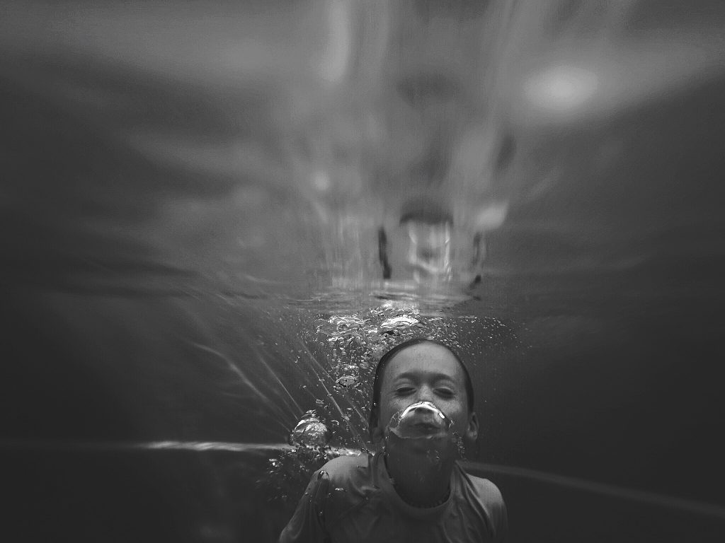 black and white underwater photo of a girl in a swimming pool